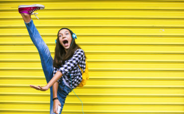 barn dansar mot en gul husfasad och med hörlurar på sig