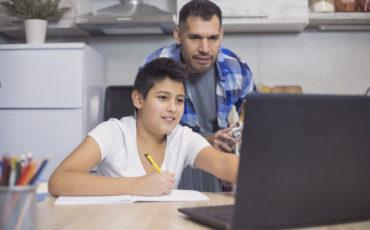 Pappa hjälper son med läxorna