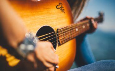 Bild på en person som spelar guitarr