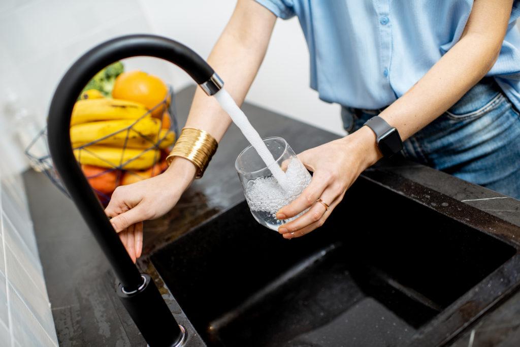 En person fyller ett vattenglas med vatten från en vattenkran.