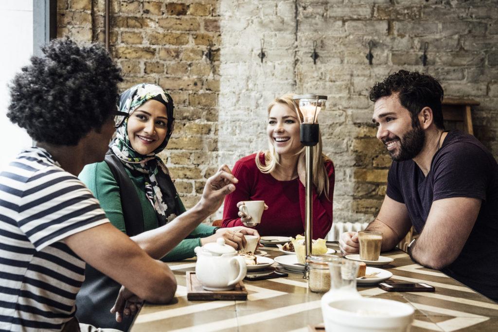 Fyra personer som sitter runt ett bord och pratar