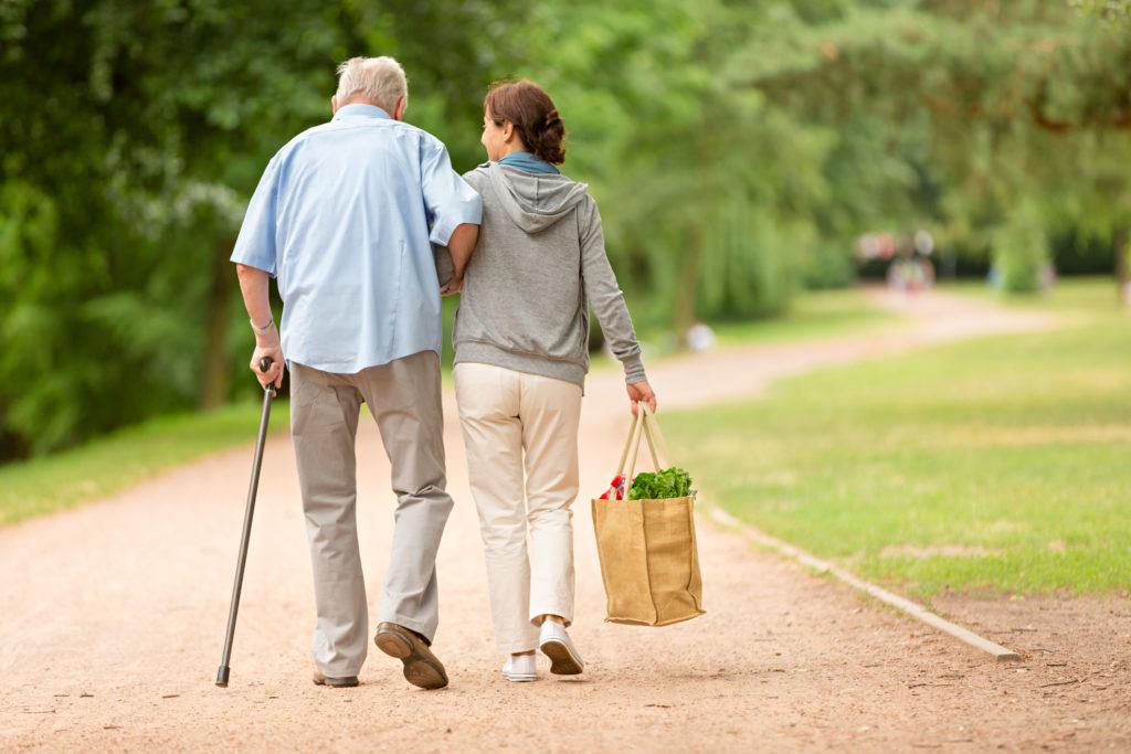 Bild på en yngre person som hjälper en äldre person. De går i en park.