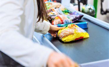 En bild på en hand som för varor över ett varuband i en matvaruaffär