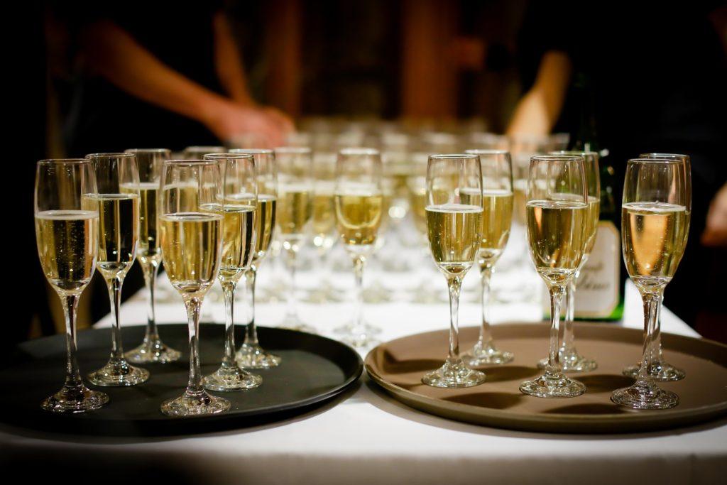 Brickor med champagneglas fyllda med en gul dryck