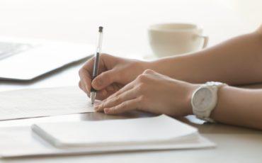 händer som skriver på ett papper