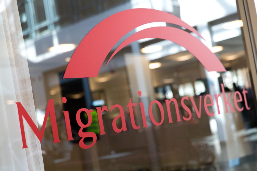 Bild på en dörr in till MIgrationsverket som har myndighetens logotypMigrationsverket
