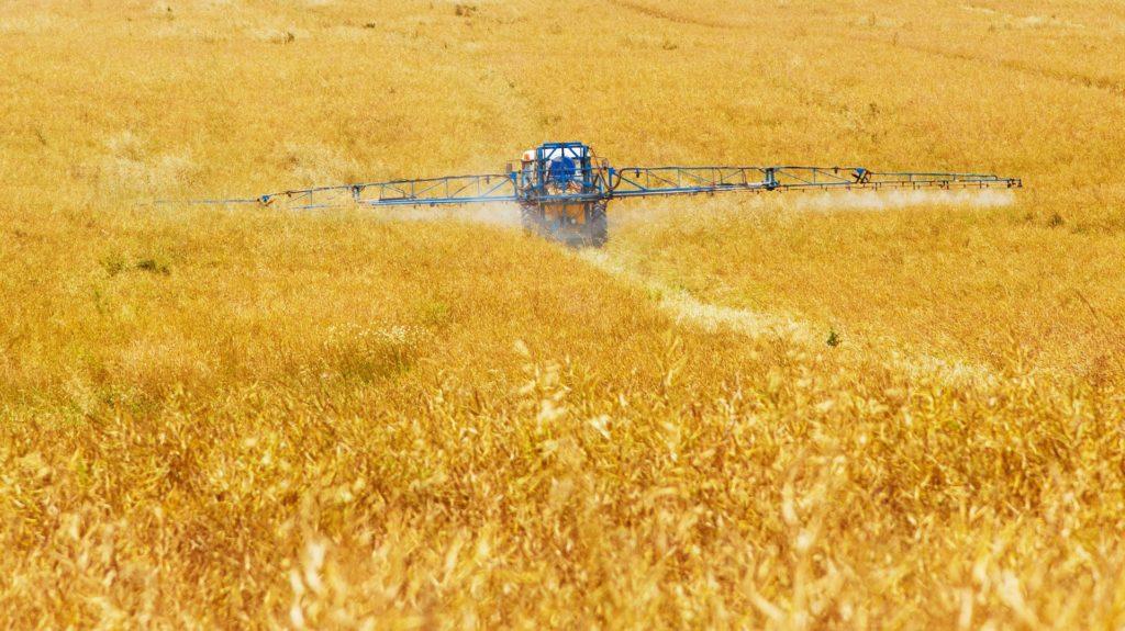 Lantbruksmaskin ute på ett gult fält