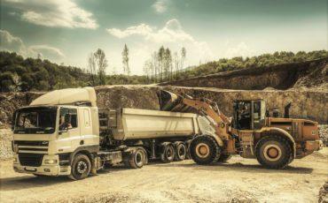 Lastbil och grävmaskin i arbete