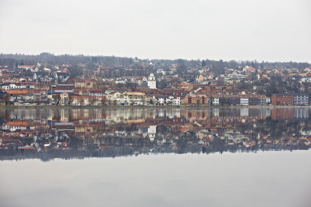 Spegelblankt Åsundenvatten och sedan en stadsvy.