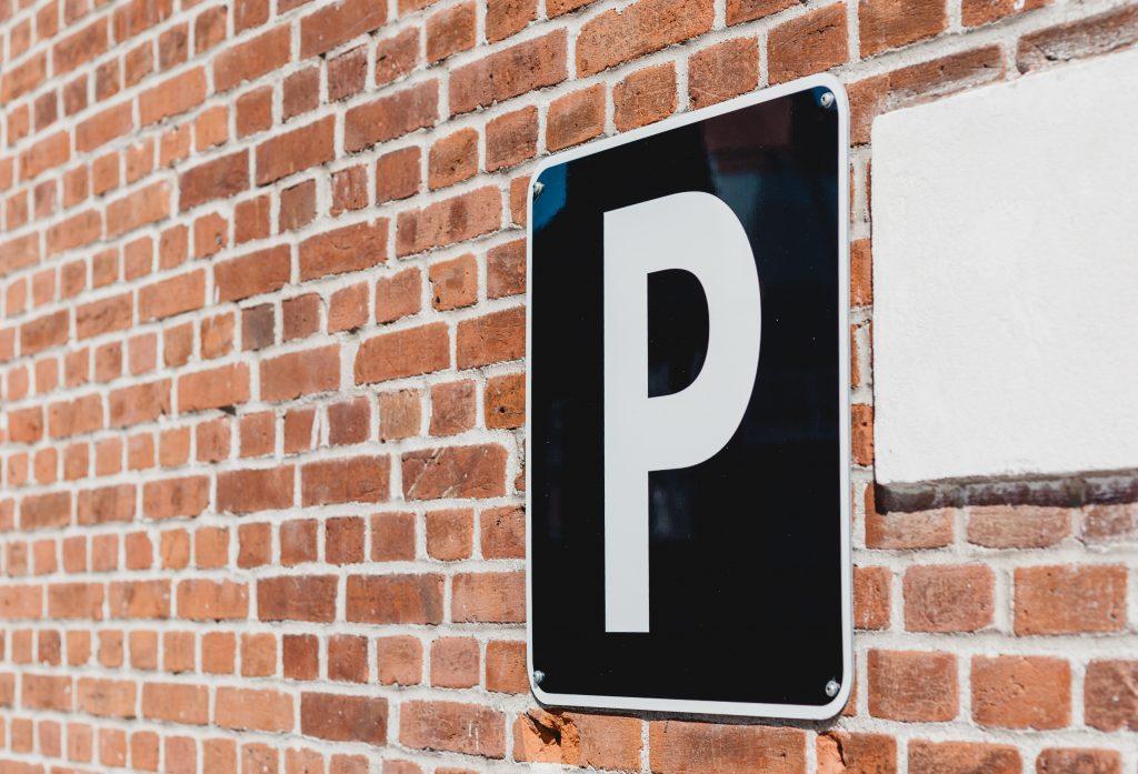 Bild på en parkeringsskylt framför en tegelvägg