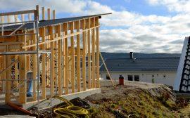 Bild på ett villabygge där endast trästommen byggts. i bakgrunden ett färdigbyggt vitt hus.