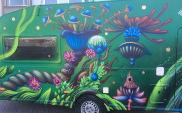 Bild på en husvagn målad i grön bakrund med konstnärliga figurer och växter.