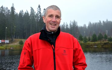 Bild på en man i 50-årsåldern som står vid en damm i röd jacka. Han ler.