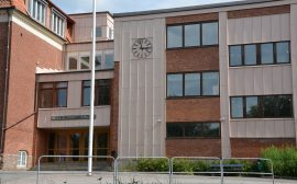Bild på en skolentré med en klocka. Ovanför dörren står Stenbocksskolan.