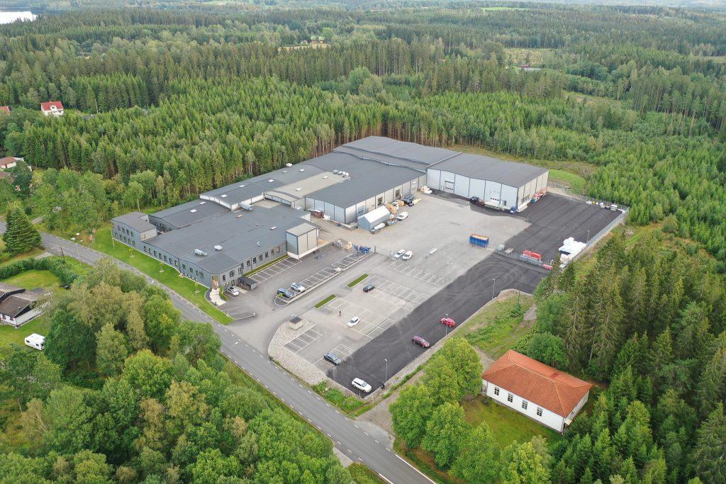 Flygvy över en stor industribyggnad med granskog runt omkring.