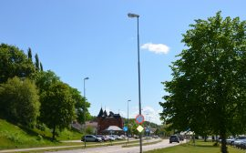 bild på en väg med grönska runt omkring. i bakgrunden en tegelbyggnad med svart torn.