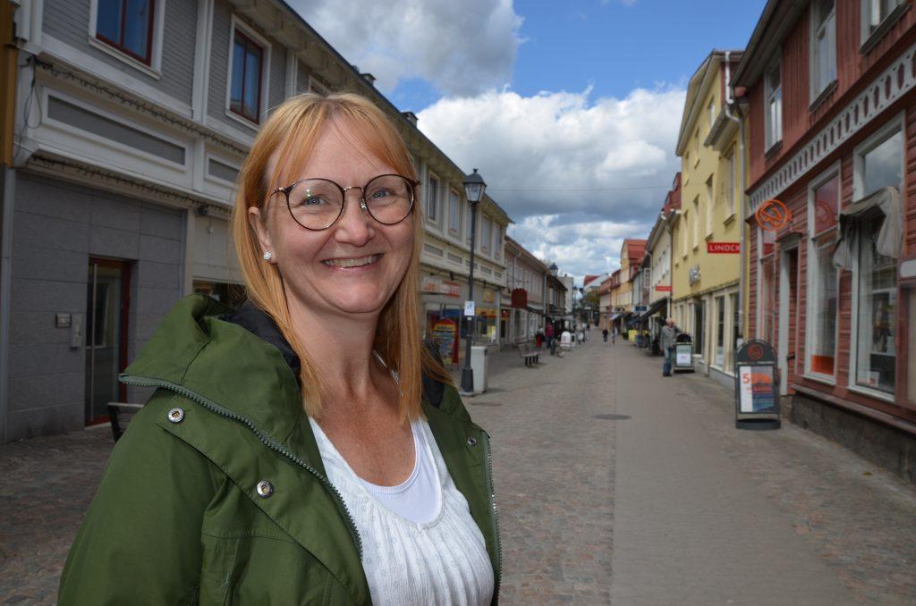 Bild på medelålders kvinna i grön jacka som leende står med gågatan i Ulricehamn i bakgrunden. Linda Larsson Järleklint på gågatan i Ulricehamn.