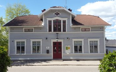 Bild på ungdomens hus, en grå träbyggnad i två våningar med röd dörr och vita fönster.