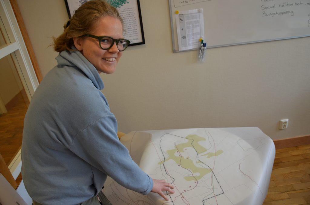 Bild på en leende kvinna i tjugoårsåldern med glasögon, blå tröja som håller en karta.