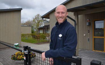 Bild på leende man med rakat huvud som står bakom en grund utanför en grå träbyggnad.