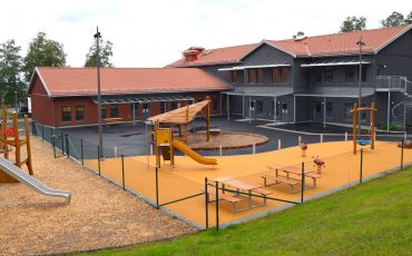 Bild på en förskola med byggnader i grått och rött. i förgrunden en färgglad utegård.
