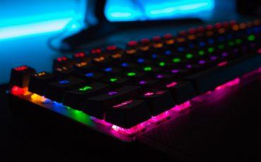 Ett tangentbord som lyser under tangenterna i blått, lila, grönt och rött.