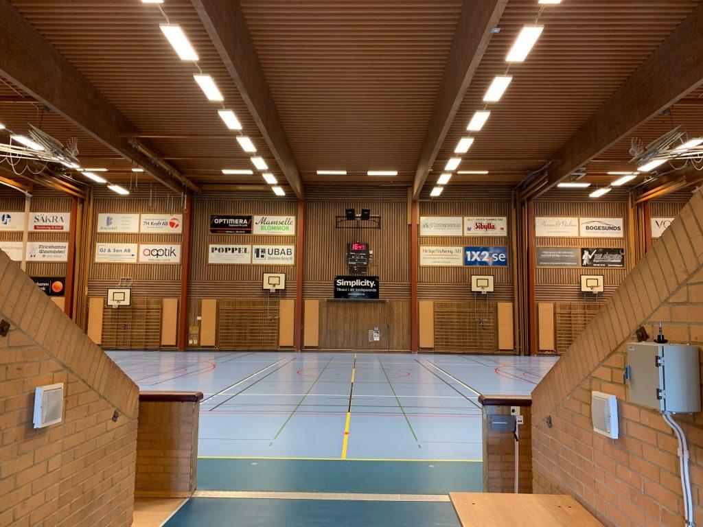 Bild på en stor idrottshall med träfärgade väggar och blått golv.
