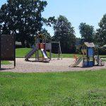 Bild på lekplats vid grönytor, klätterställning och en klättervägg.