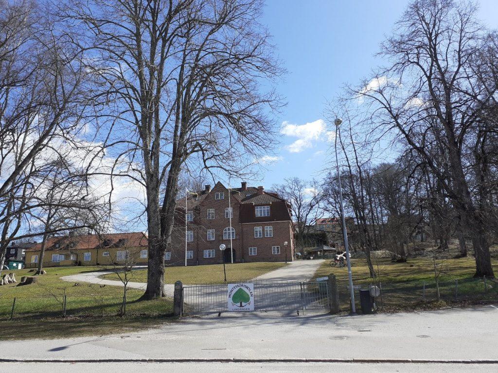 Bild på montessoriskolan vid lindängsvägen med skolans park och grind i förgrunden en solig vårdag