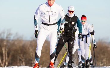 Bild på fyra elever från skidgymnasiet som åker skidor på snö.