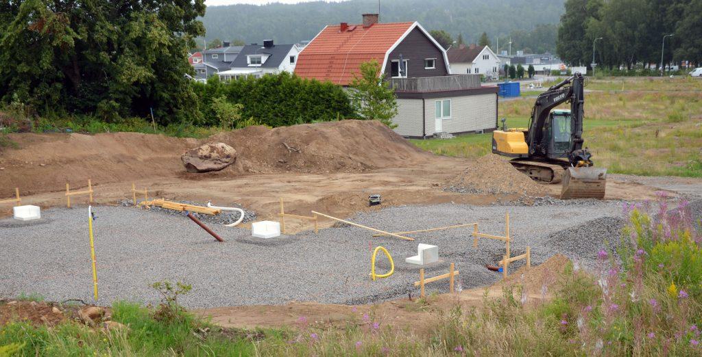 Bild på en tomt som håller på att markberedas av en grävskopa. ett färdigbyggt hus i bakgrunden.