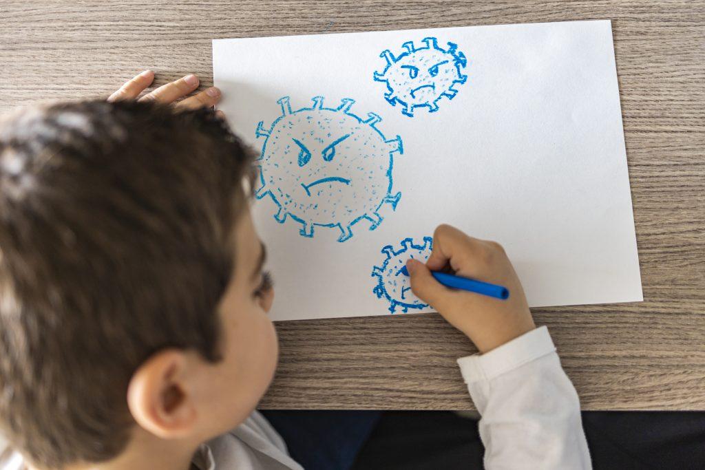 Bild på pojke som målar arga coronavirusgubbar på ett vitt papper