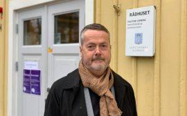 Gustaf Olsson framför rådhusets gula fasad