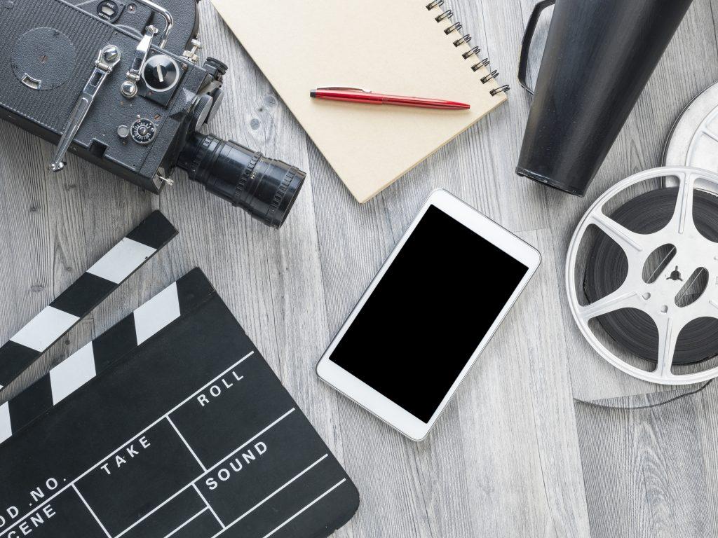Filmkamera, anteckningsblock och filmklappa på ett bord.