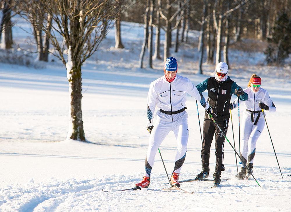 Två längdskidåkare åker skidor utomhus.
