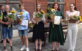 Bild på fem personer som står med blommor och diplom efter en prisutdelning