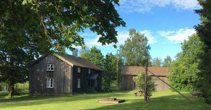 Bild på en äldre gård med två grå träbyggnader i grönska