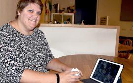 Bild på Ida Hoffren, en korthårig kvinna som sitter vid ett bord med den ipad och ler in i kameran.