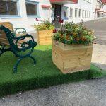 Två blomsterlådor och två små bänkar byggda i återvunnet material. Blomsterlådorna är fyllda med blommor och annat som grönskar.